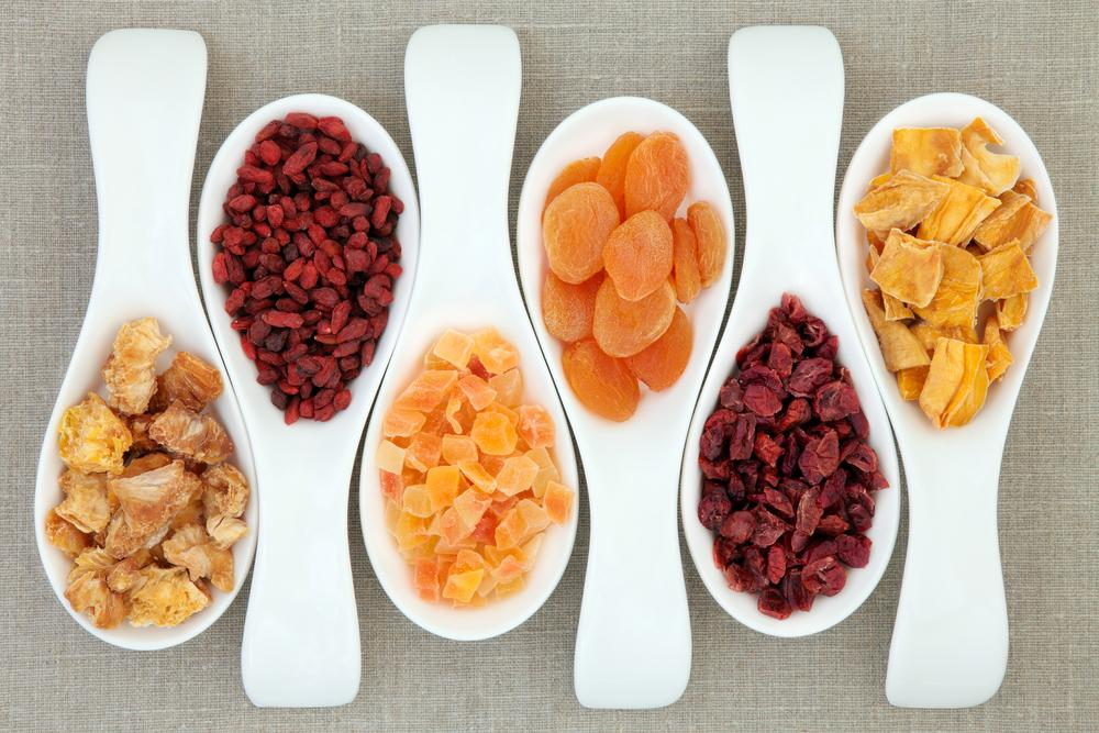 white spoons filled with dried fruit
