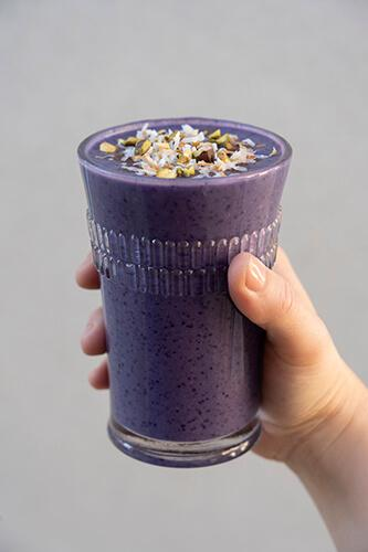 Hand holding Jenny Craig Blueberry Cauliflower Smoothie in glass