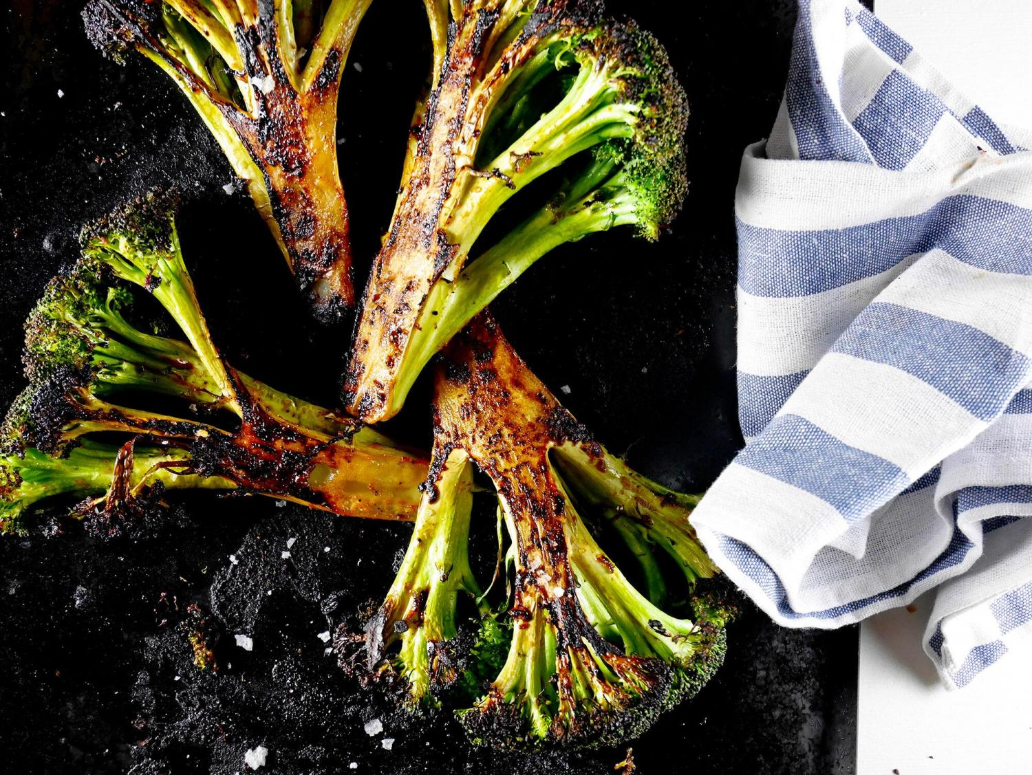 roasted broccoli on black plate with blue and white striped cloth napkin