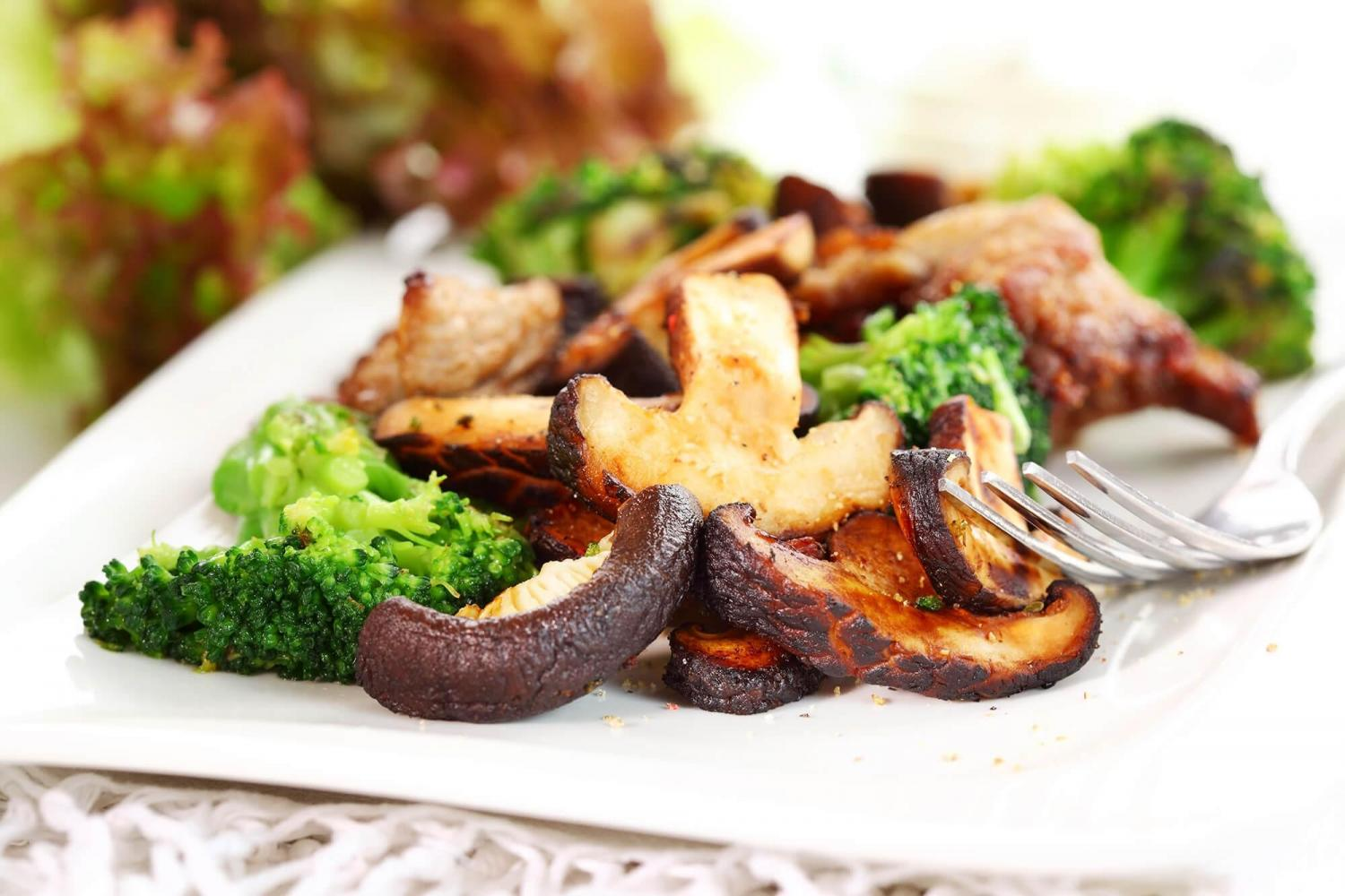 stir fry broccoli and mushrooms on white plate with fork