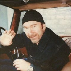 The Edge inside his Merc