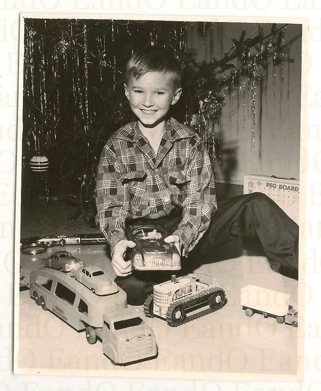 Christmas tree boy playing with cast iron and die-cast toys.jpg