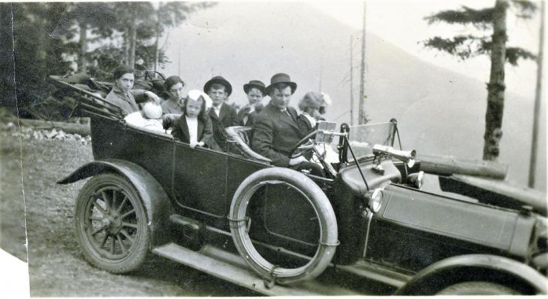 7088 Hector McKinnon and family in automobile on mountain road.jpg