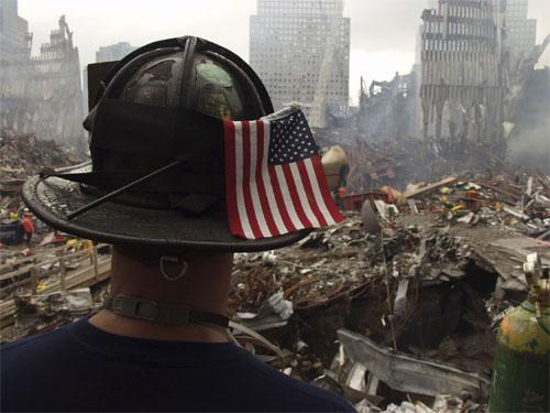 A-fireman-stands-amid-rubble-with-a-911-flag-on-his-helmet.jpg