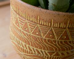 Detail, stoneware planter with yellow mishima wax resist decoration