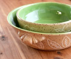 Pie plate set in speckled clay with green interior and slip inlaid decoration on exterior